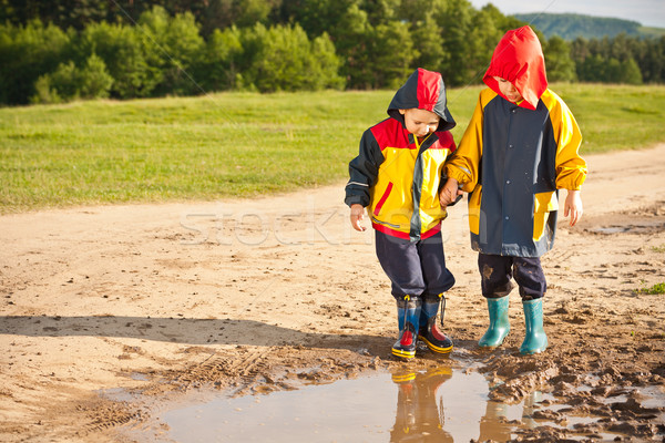 Two boys walking through a mud puddle Stock photo © grafvision