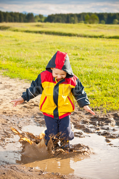 Wenig Junge springen Schlamm Pfütze Wasser Stock foto © grafvision