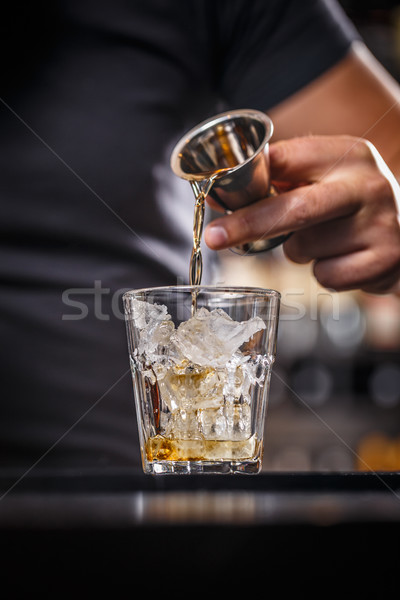 Barman is pouring alcohol from a jigger Stock photo © grafvision