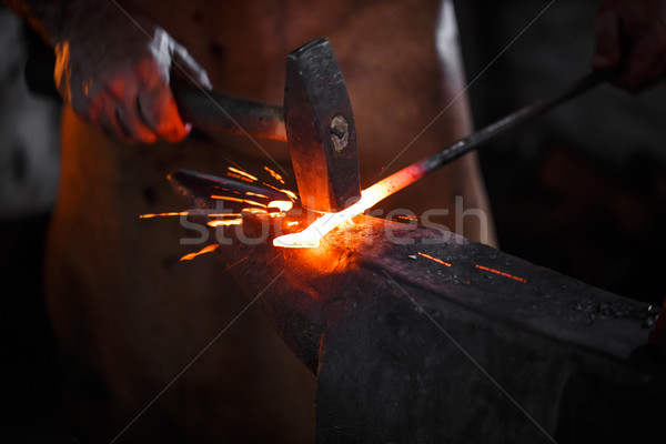 Blacksmith manually forging the molten metal  Stock photo © grafvision