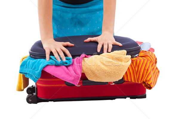 Woman crammed full of clothes in red suitcase Stock photo © grafvision