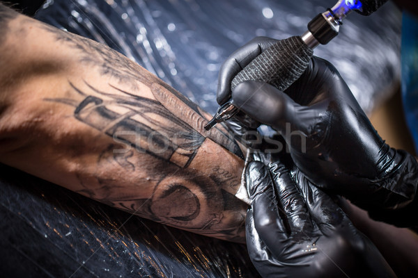 Hands of the artist tattooing Stock photo © grafvision