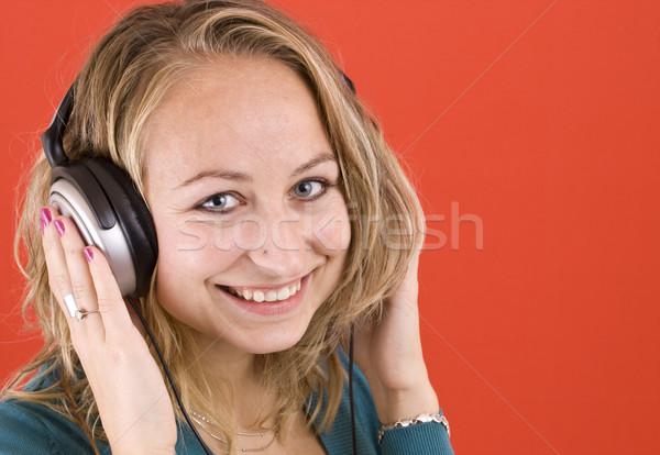 Menina fones de ouvido mulher ouvir música vermelho fundo Foto stock © grafvision