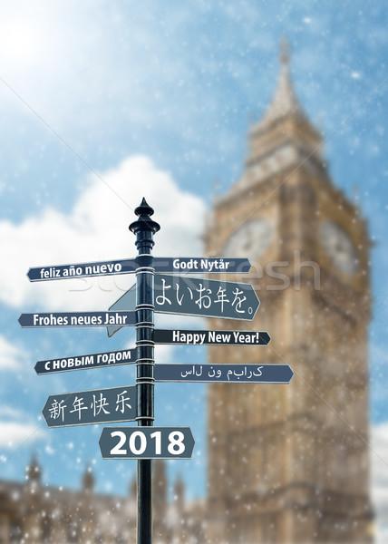 Poste indicador feliz año nuevo muchos idiomas grande reloj Foto stock © grafvision