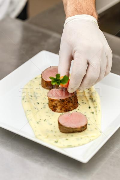 Chef garnishing meat plate Stock photo © grafvision