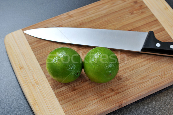 Two limes on a wooden plate and a knife  Stock photo © gravityimaging