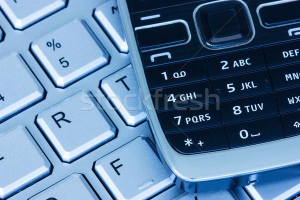 Phone on keyboard in blue tint  Stock photo © Grazvydas