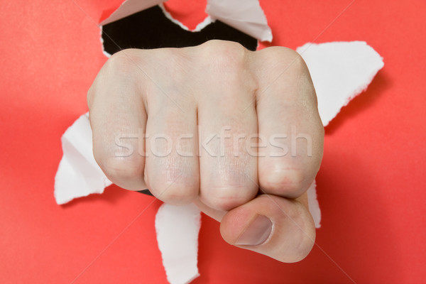 Hand punching through red paper  Stock photo © Grazvydas