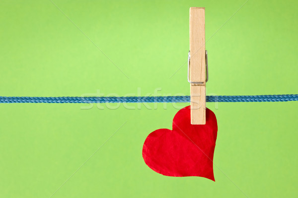 red heart hung  over a green background Stock photo © Grazvydas