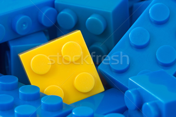 yellow plastic brick in a middle of blue ones Stock photo © Grazvydas
