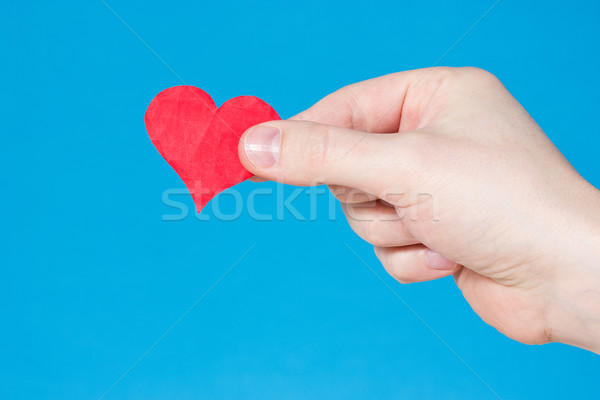 Hand with heart on blue background Stock photo © Grazvydas