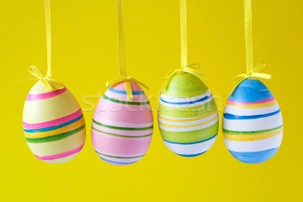 easter eggs hung on yellow background Stock photo © Grazvydas