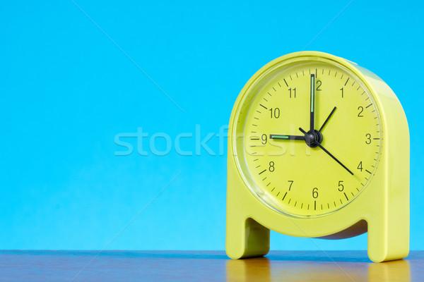 alarm clock  against blue background Stock photo © Grazvydas