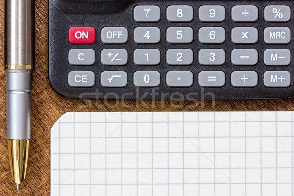 Stock photo: Calculator, pen and notepad on the table