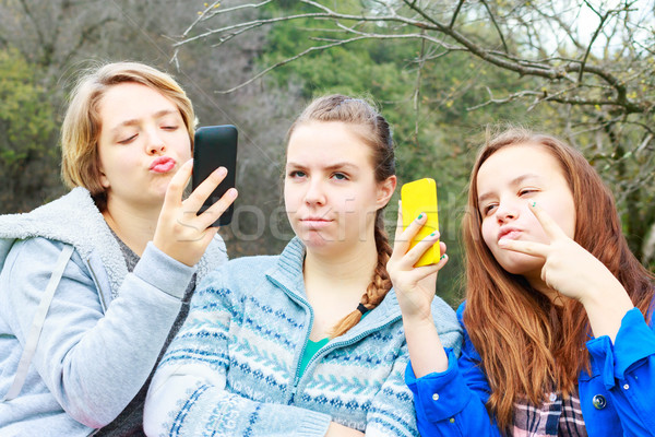 Two Girls Doing Selfies One Alone Stock photo © gregorydean