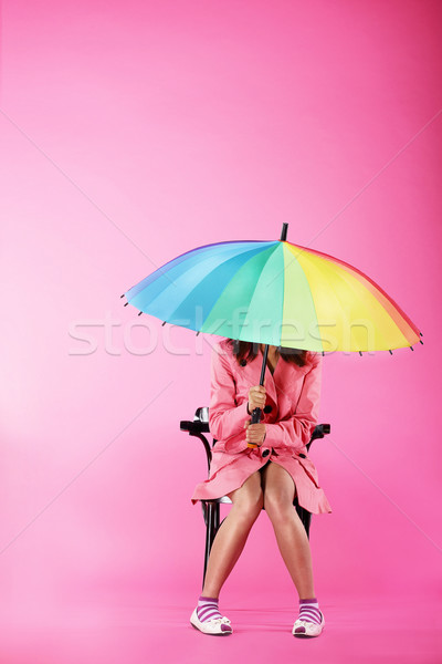 Vogue. Woman in Pink Coat sitting with Colorful Umbrella Stock photo © gromovataya