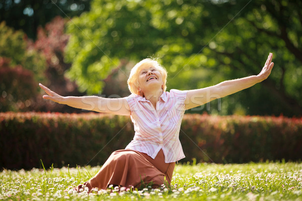 Gladness. Meditation. Mature Pleased Woman Relaxing with Outspread Arms Stock photo © gromovataya
