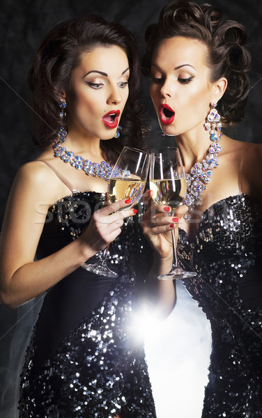 Two beautiful women with champagne singing christmas songs Stock photo © gromovataya