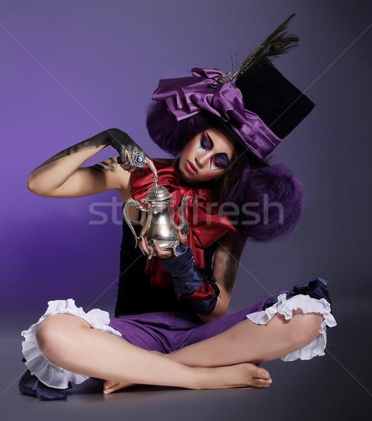 Performance. Entertainer sitting in Cylinder Hat with Bow Knot and Feathers Stock photo © gromovataya