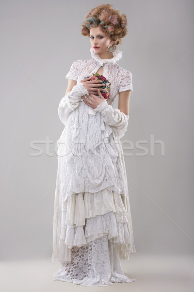 Elegance. Gorgeous Fashion Model in Long Gown and Bouquet of Flowers Stock photo © gromovataya