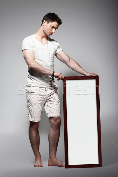 Shoeless Man Displaying White Board with Blank Space Stock photo © gromovataya