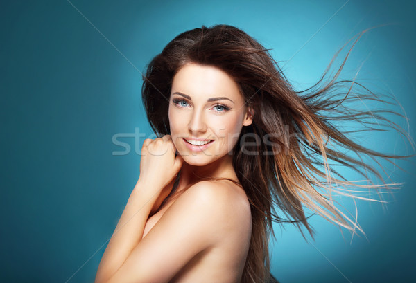 Beautiful young woman with long brown flying hair on  blue backg Stock photo © gromovataya
