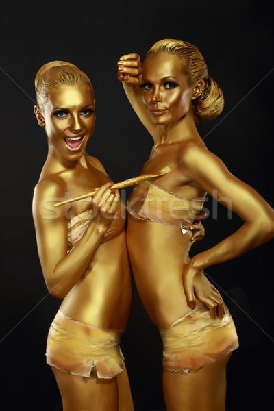 Fancy Dress Party. Couple of Women with Golden Metallic Painted Skin. Creativity Stock photo © gromovataya