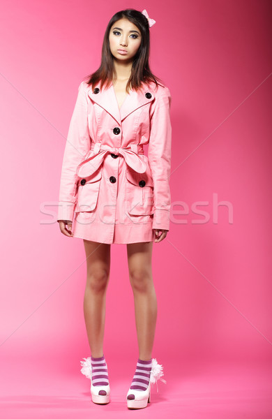 Stock photo: Young Asian Female Fashion Model in Pink Coat standing in Studio