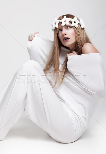 Stock photo: Actress in theatrical pose sitting in white cloth studio shot