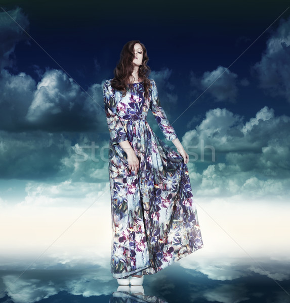 Fantasy. Luxurious Woman in Variegated Dress over Blue Sky Stock photo © gromovataya