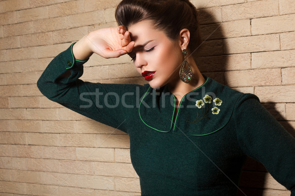 Aristocratic Brown Hair Sad Woman in Green Dress over Brick Wall Stock photo © gromovataya