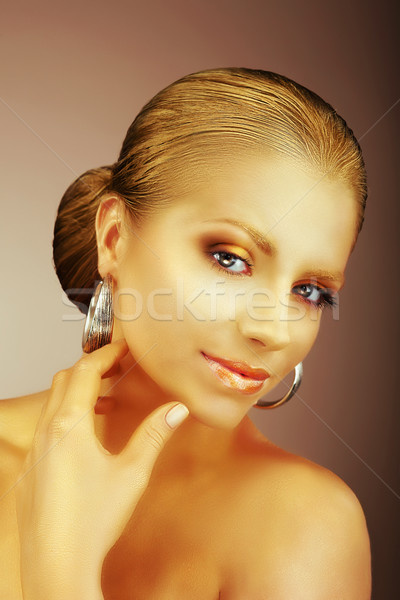 Fascinating Lady with Silver Earrings and Silky Golden Skin Stock photo © gromovataya