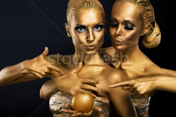 Masquerade. Enjoyment. Two Glossy Women with Golden Body Art. Glamor Stock photo © gromovataya