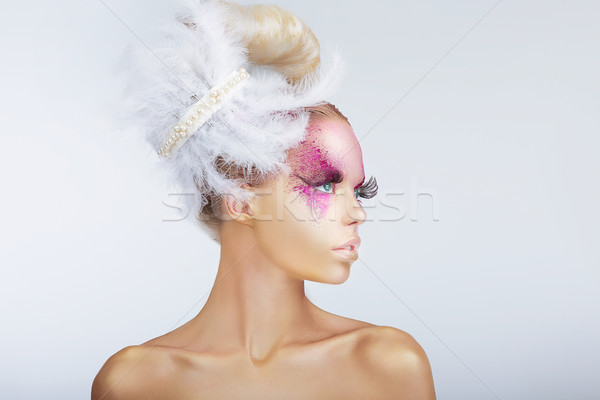 Creativity. Glamorous Fashion Model with Fancy Hair-do with Feathers Stock photo © gromovataya