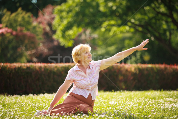Meditation. Graceful Old Woman in the Park Stretching her Hand Stock photo © gromovataya