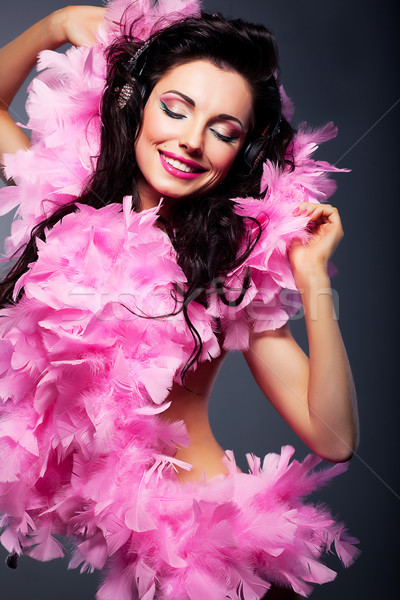 Elated positive woman in pink dress listening to the music Stock photo © gromovataya