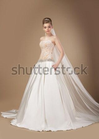 Beautiful woman in wedding dress over studio background Stock photo © gromovataya