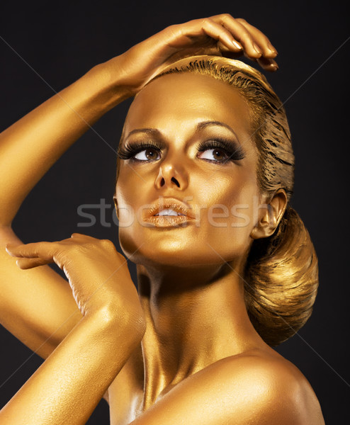 Reflexion. Portrait of Glossy Woman with Bright Golden Makeup. Bronze Bodypaint Stock photo © gromovataya