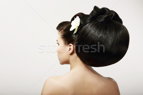 Haircare. Backside of Fashion Model with Creative Hairstyle. Smooth Healthy Black Hair with Flower.  Stock photo © gromovataya