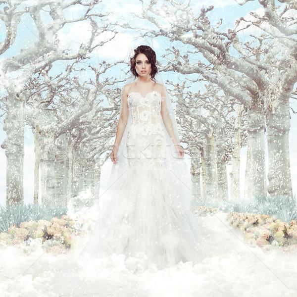 Fantasy. Matrimony. Bride in White Dress over Frozen Winter Trees and Snowflakes Stock photo © gromovataya