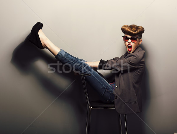 Funny girl sitting in sunglasses on chair in studio - vintage style Stock photo © gromovataya