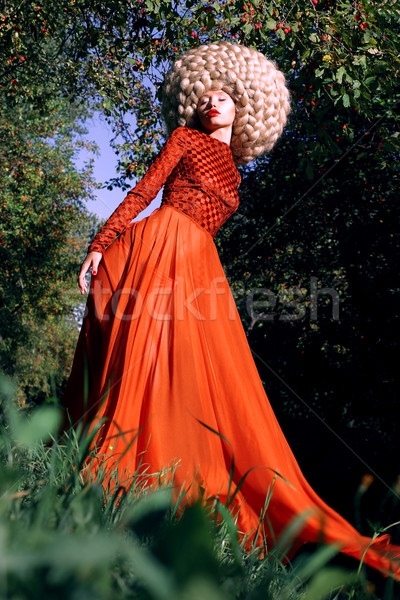 Fantasy. Artistic Stylized Woman in Trendy Red Dress and Big Frizzy Wig Stock photo © gromovataya