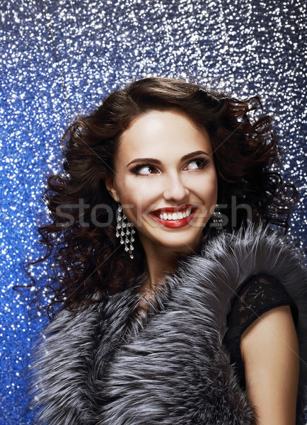 Sparkle. Beautiful Fashion Model with Shiny Earrings in Fur Vest. Toothy Smile Stock photo © gromovataya