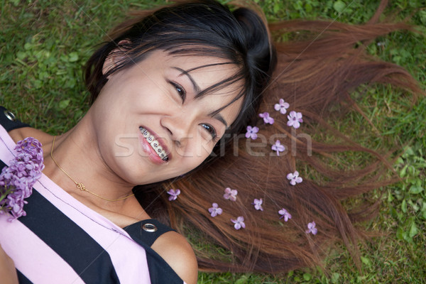 Thai womanwith a big smile laying on the grass Stock photo © gsermek