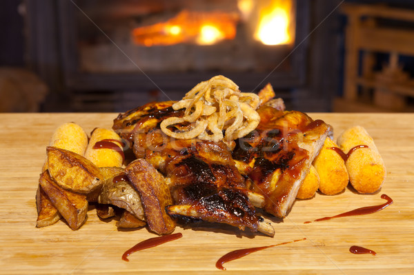 Grilled ribs topped with barbecue sauce and onion rings Stock photo © gsermek