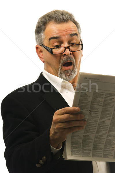 Businessman reads newspaper with a look of shock in his face Stock photo © Habman_18