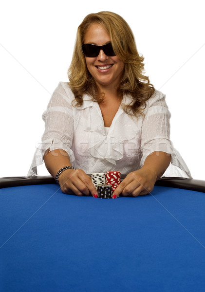 Woman pushes poker chips on blue table Stock photo © Habman_18