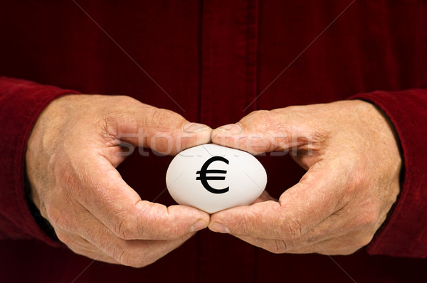 Man holds white egg with the Euro symbol written on it Stock photo © Habman_18