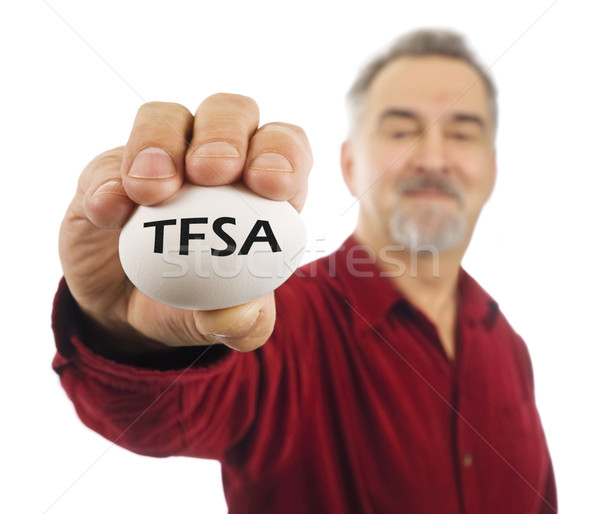 Mature man holds an egg with TFSA on it. Stock photo © Habman_18