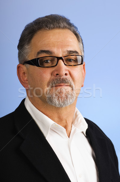 Portrait of a serious mature man with glasses against blue Stock photo © Habman_18